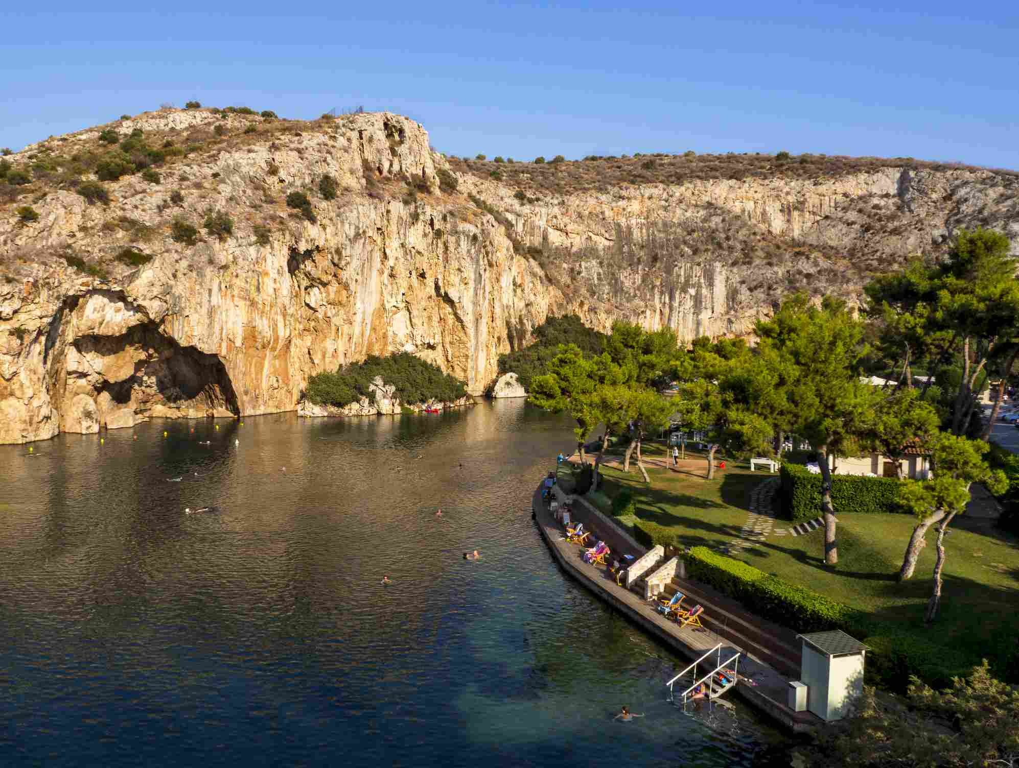 Vouliagmeni Lake in Greece with a rock formation in the background