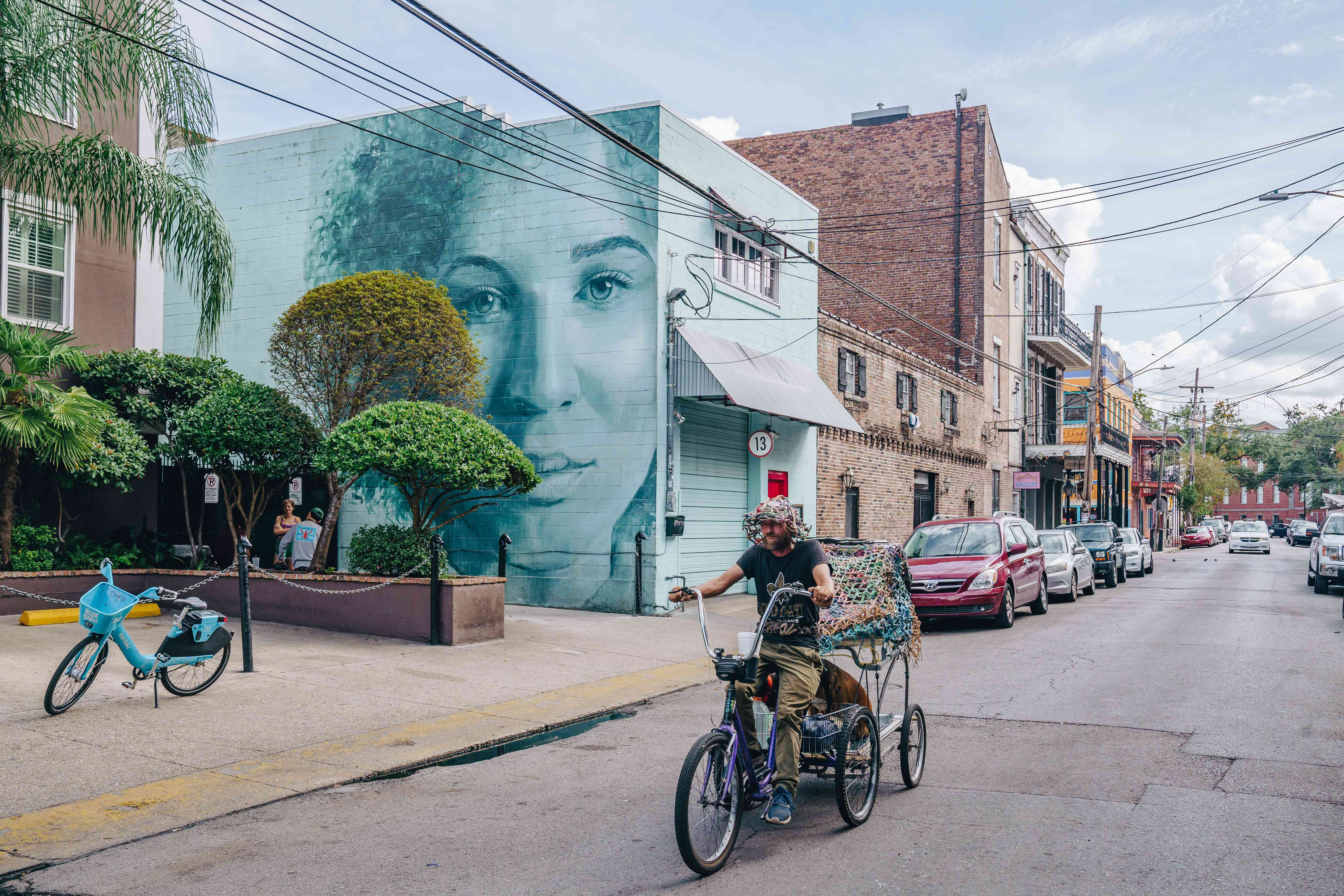 A man biking down Frenchmen street with a large portrait mural on the passing building