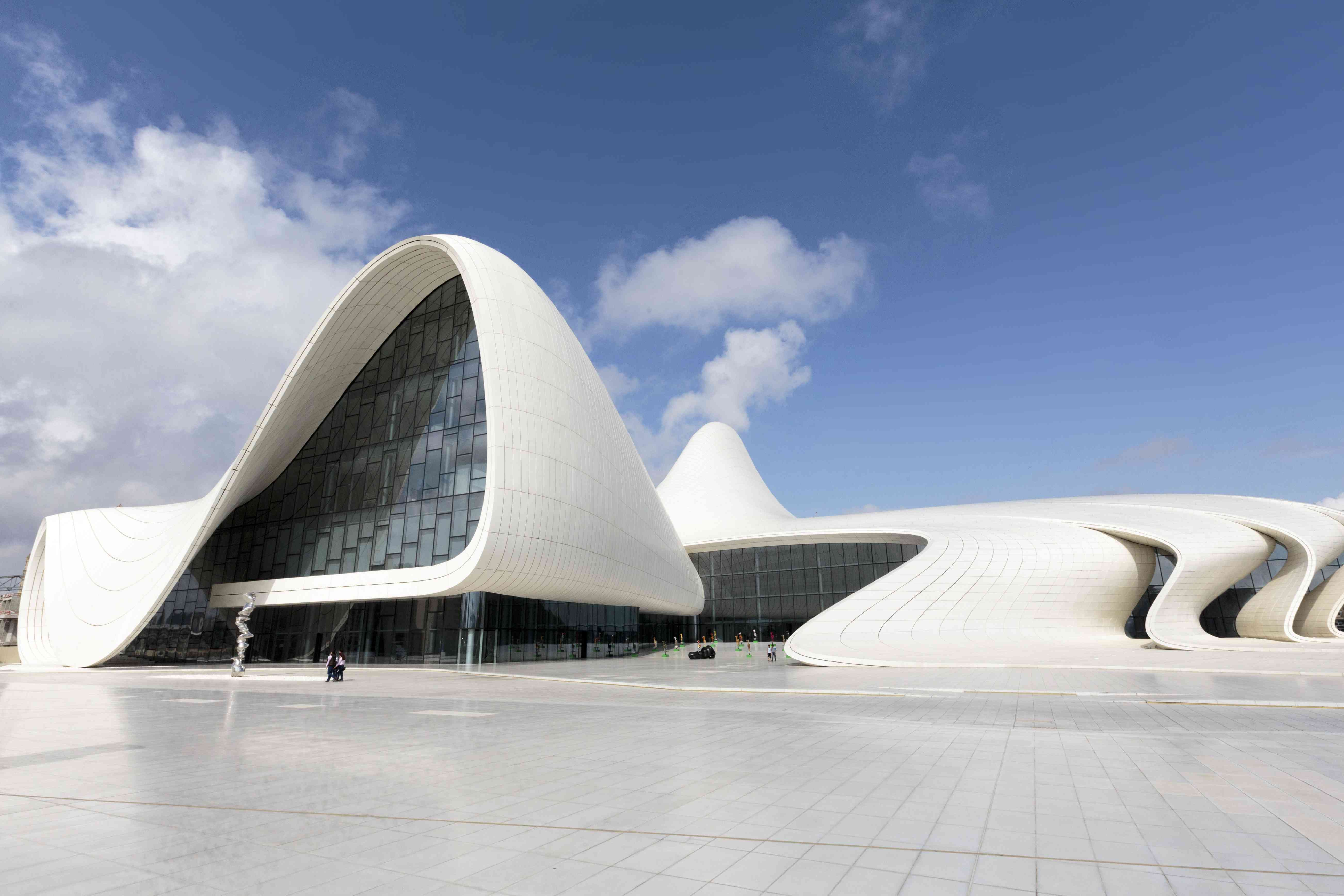 large white building with organic, curving arches and an empty white tile promenade