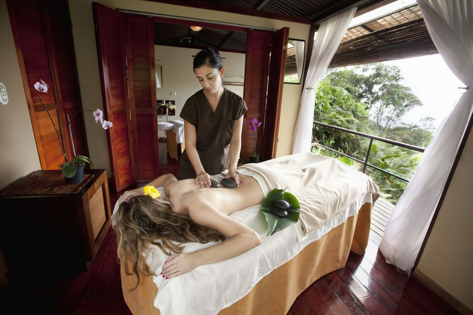 Massage therapist giving a client a hot stone treatment