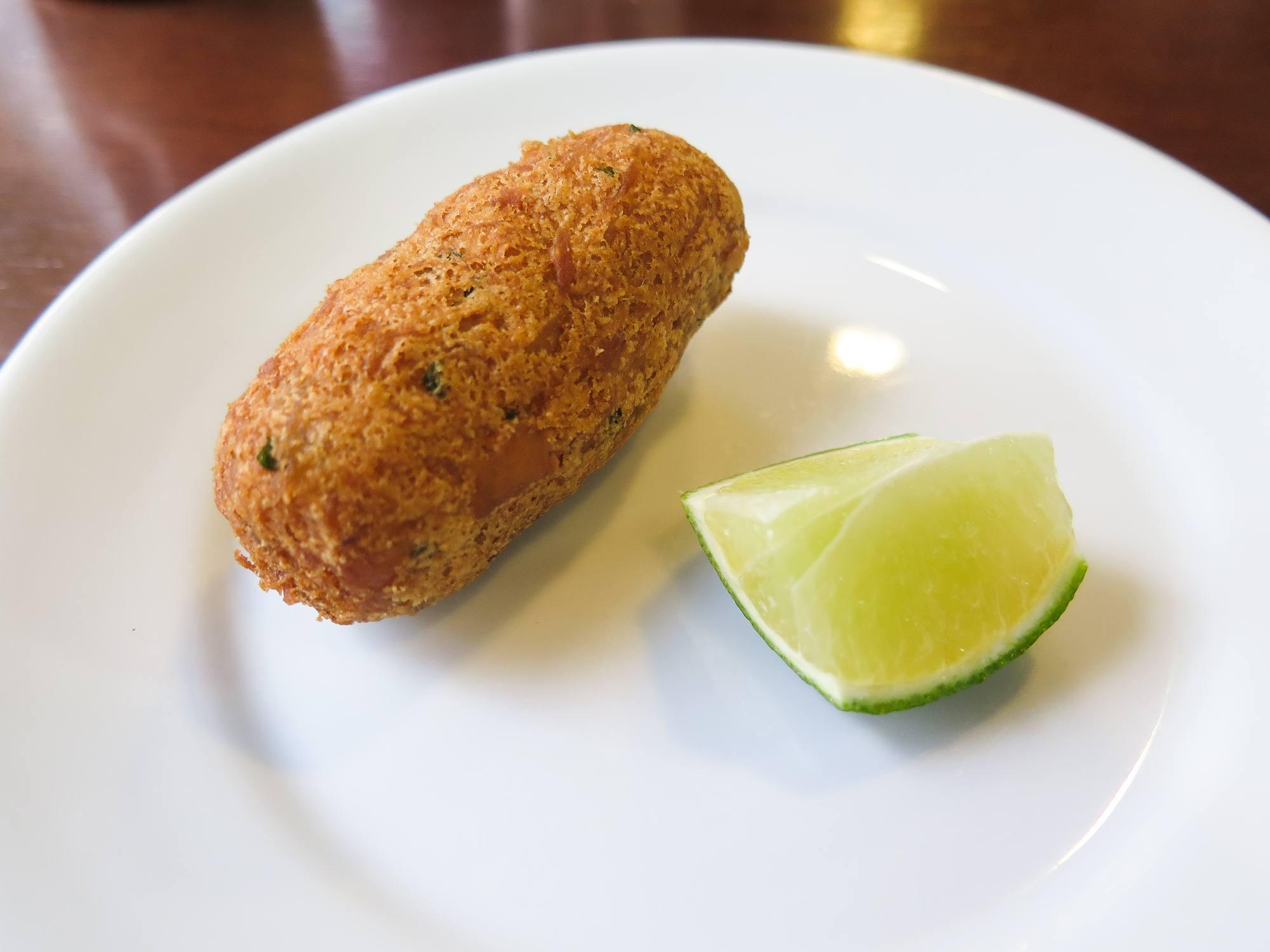 Dumpling on plat next to lime.
