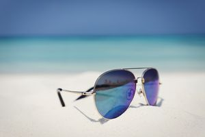 Close up aviator sunglasses in sand on sunny tropical ocean beach