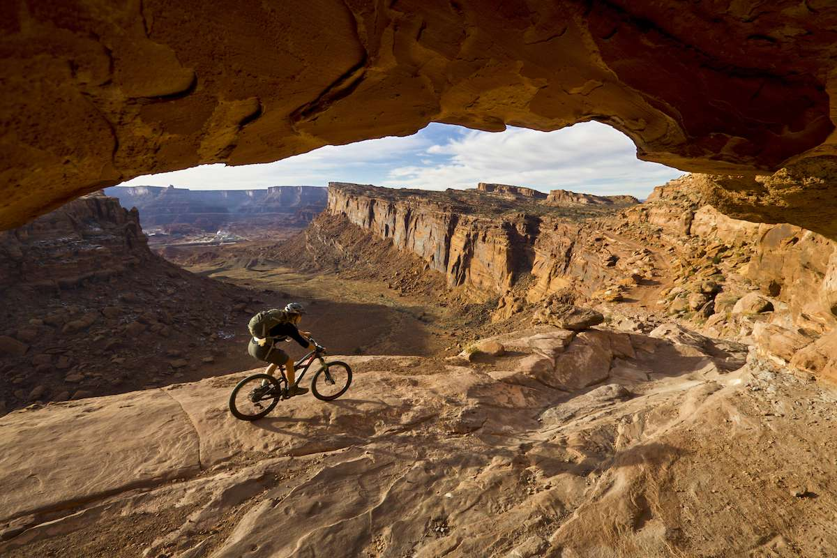 A mountain biker rides a slick rock trail with a red-rock canyon in the background.