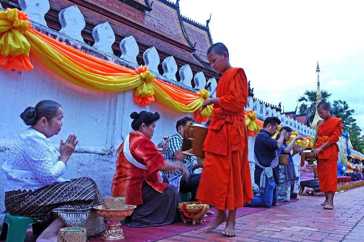 Monks collecting alms from devotees in front of Luang Prabang temple