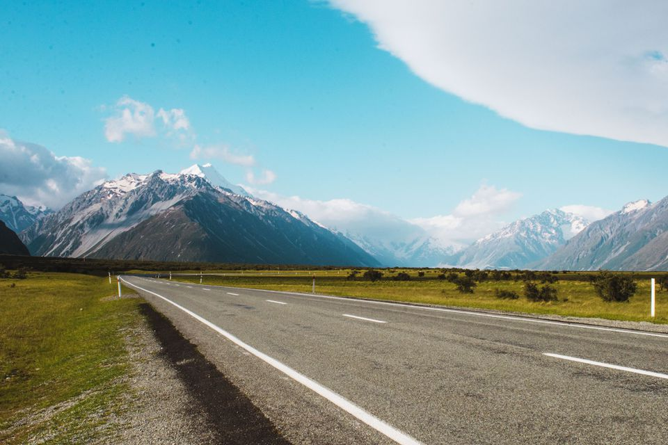 A road driving towards the mountains Aoraki National Park