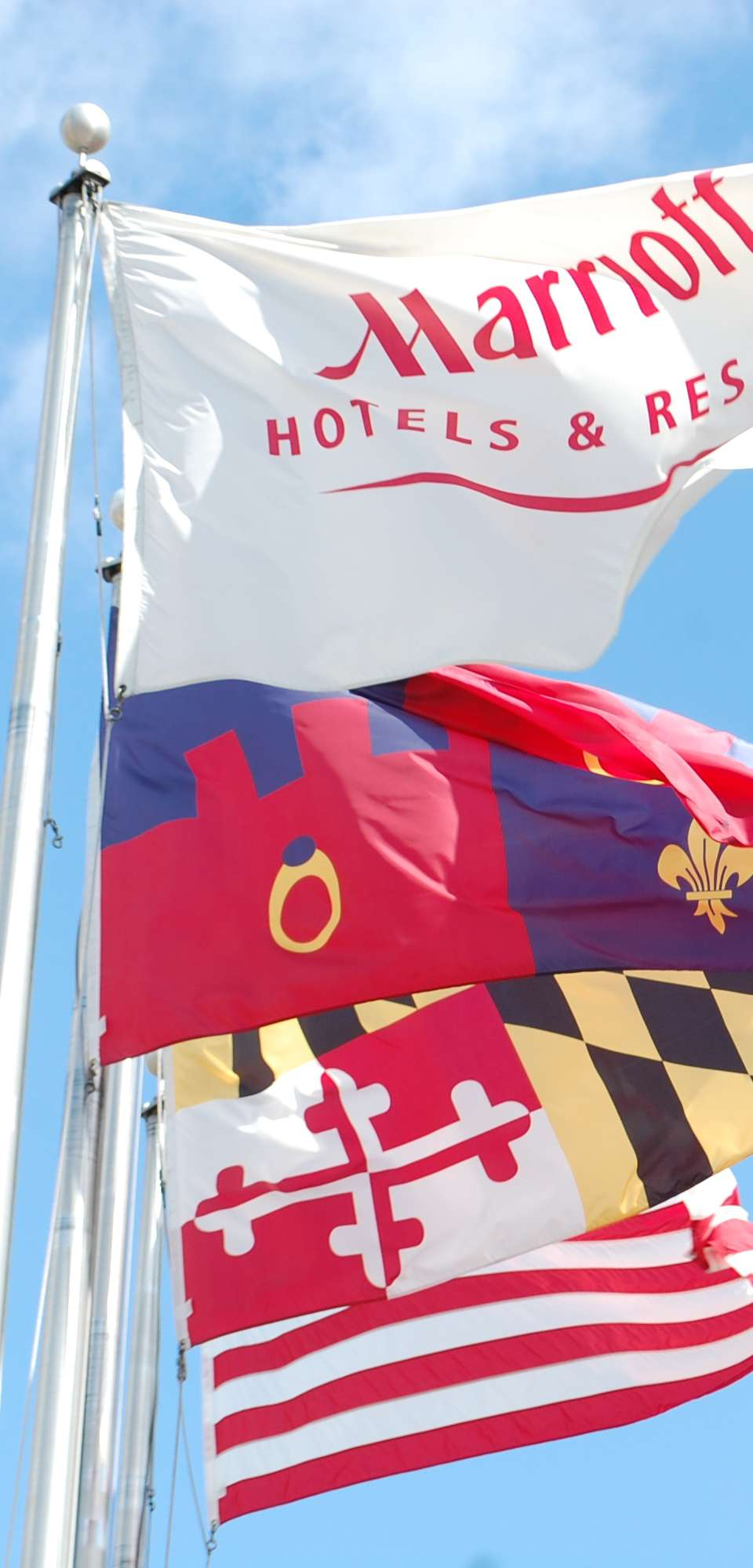 Marriott, Maryland State, and United States Flags flying against a blue sky