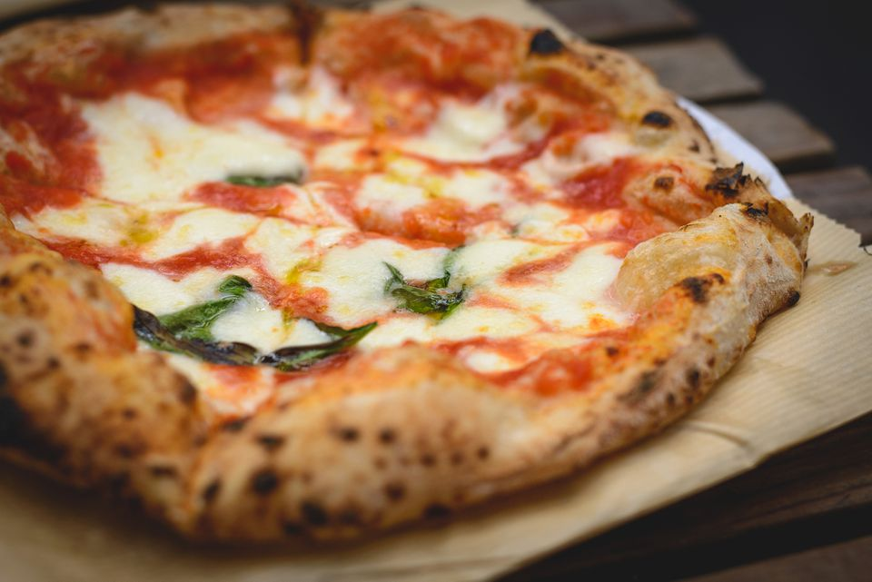 Close up view of a Margherita Neapolitan style pizza with buffalo mozzarella, tomato sauce and basil.