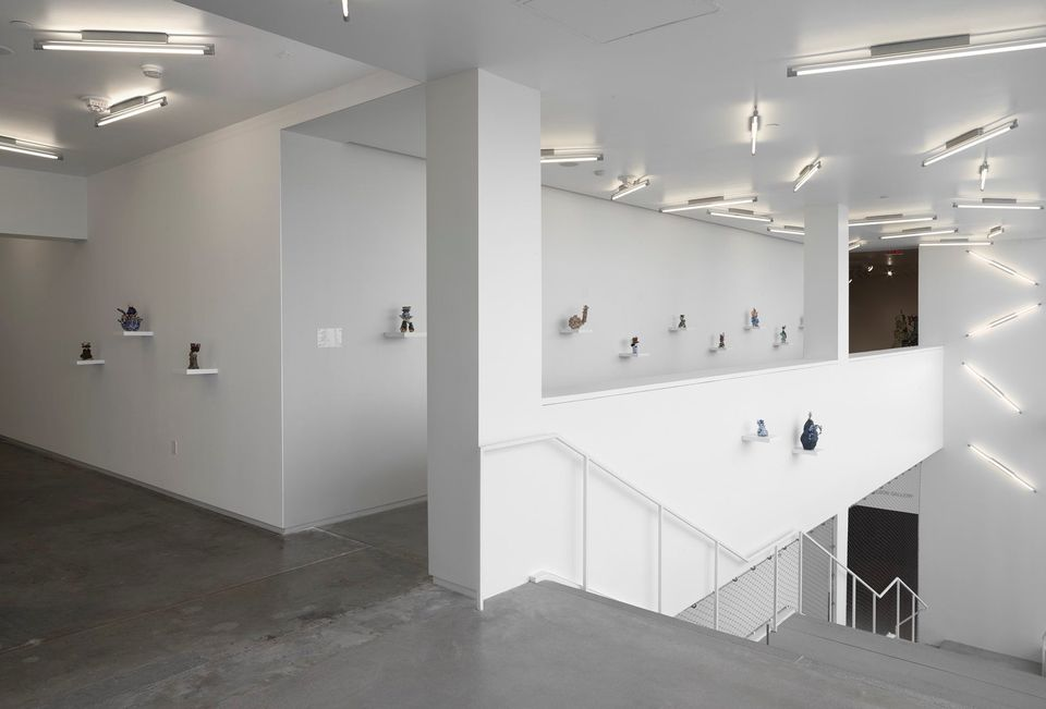 second floor of a gallery space with a gray staircase