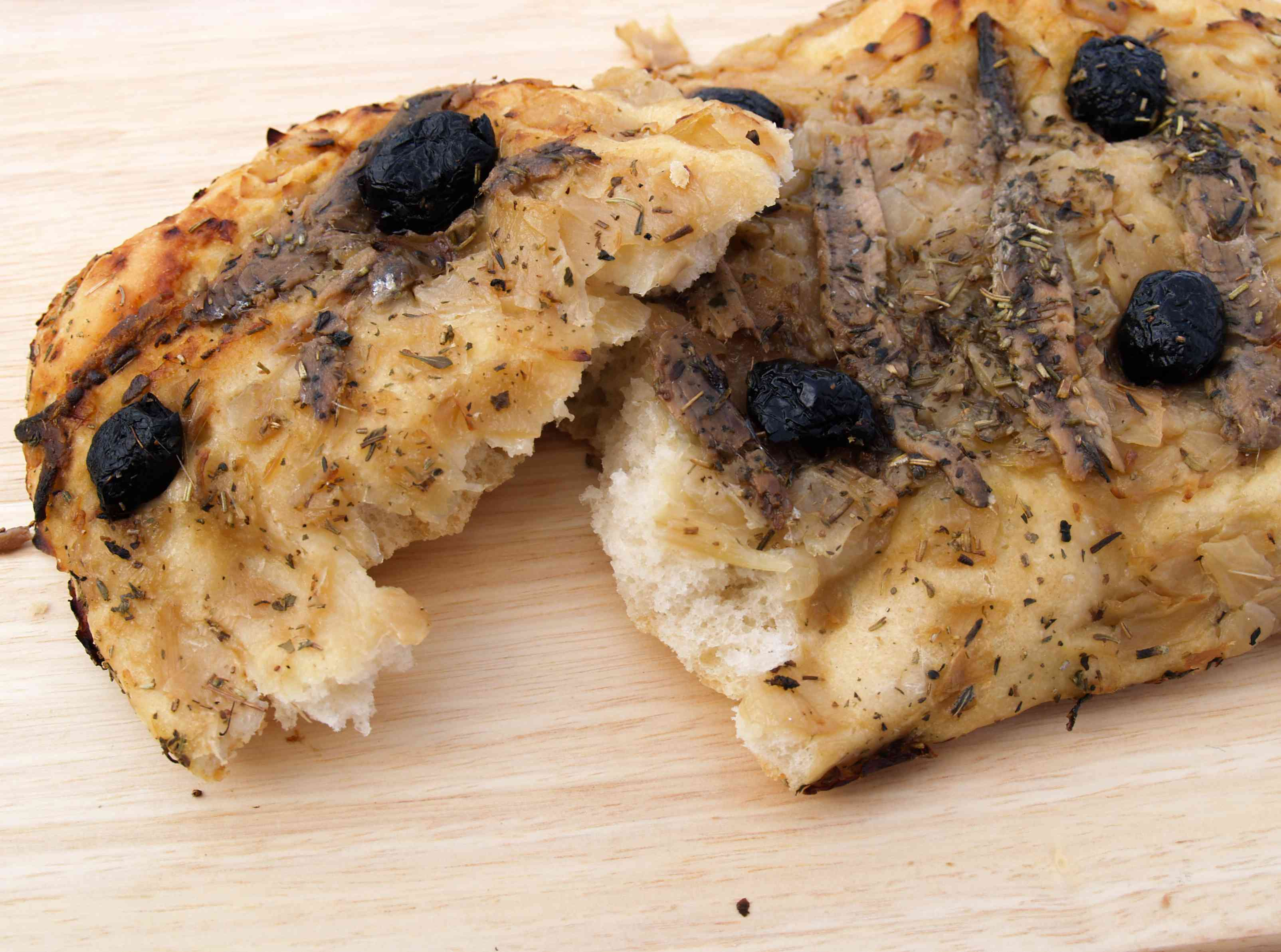 Close up of Fougasse bread baked with black olives and anchovies