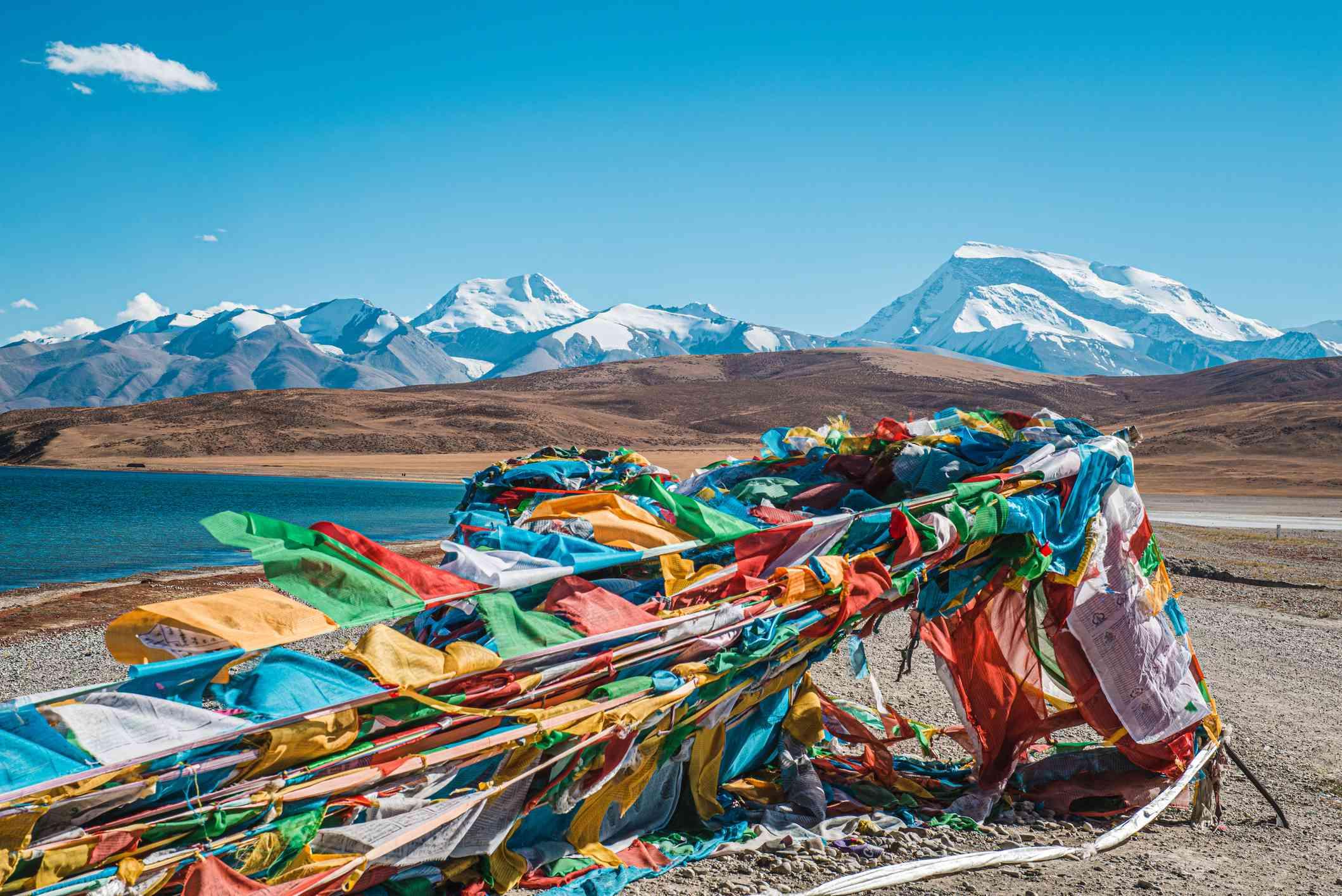 snowy mountains lake and colorful Tibetan prayer flags