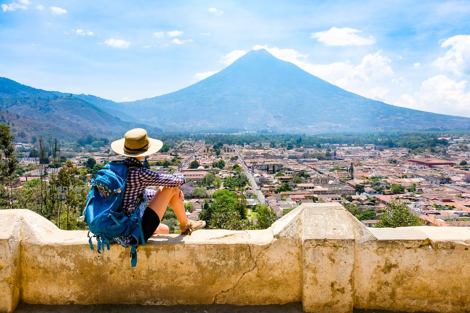 A backpacker sitting on a ledge overlooking a view of Antigua