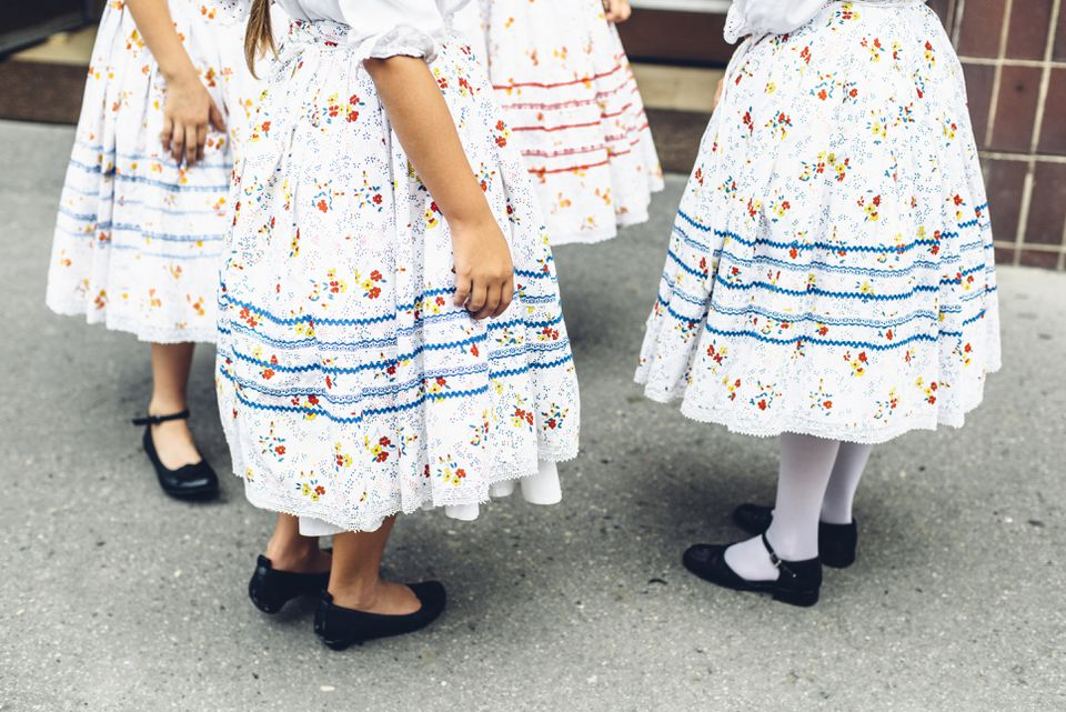 Lower parts of preteen girls in Hungarian traditional folk costumes