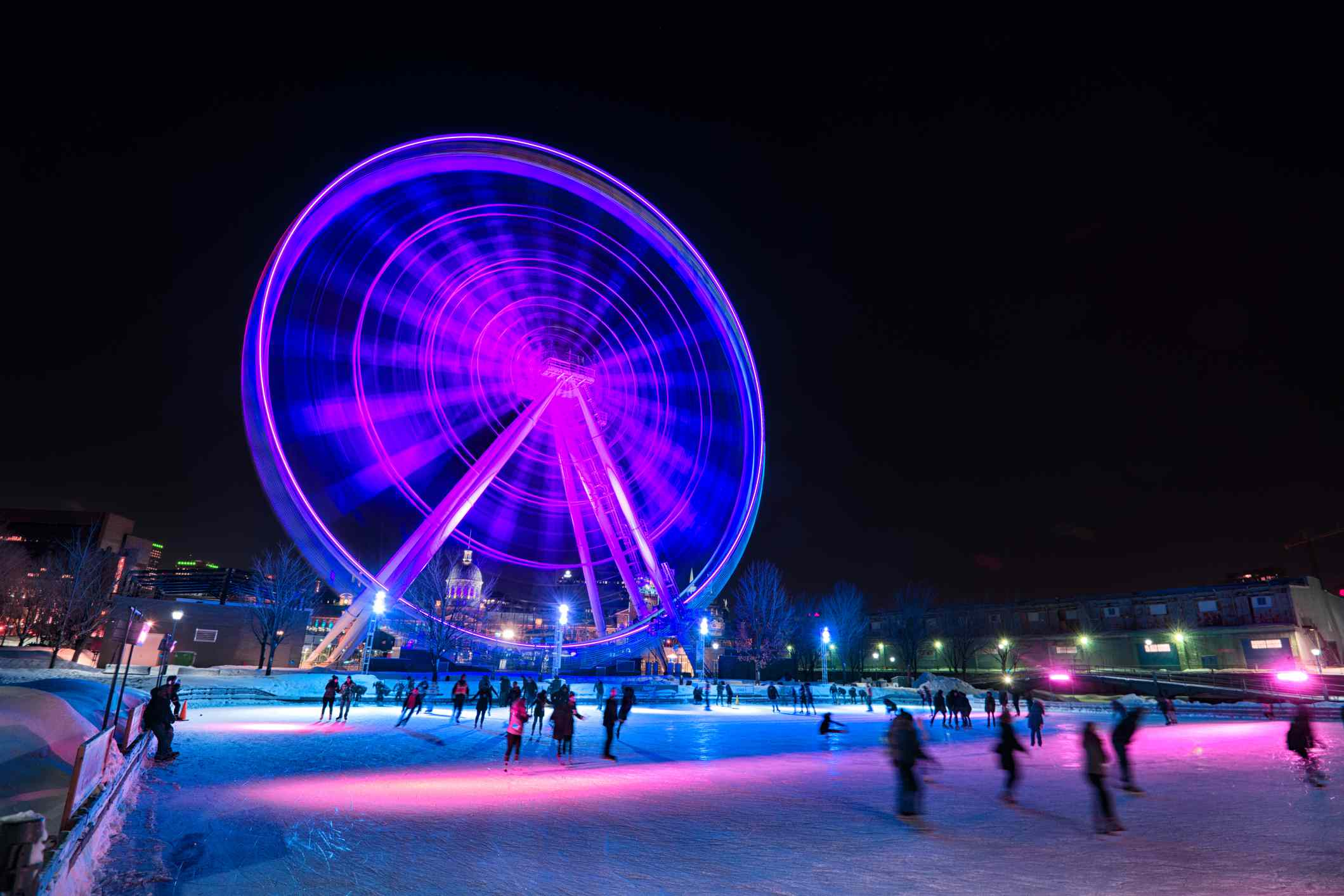 People are ice skating on the ice rink of Parc du Bassin Bonsecours.
