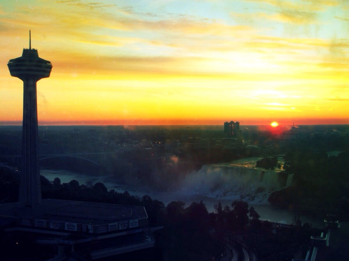 Skylon Tower With Niagara Falls Against Orange Sky