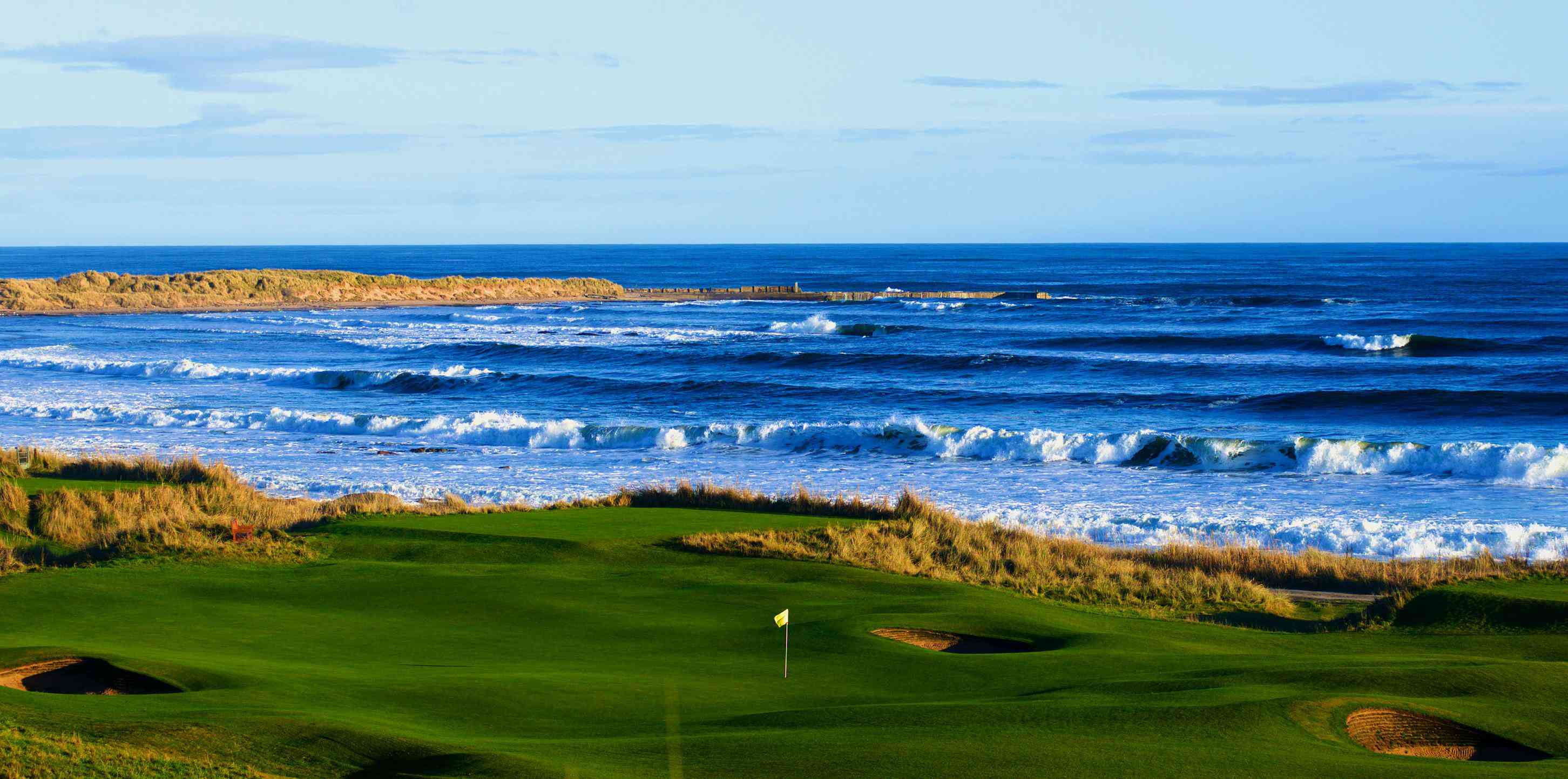 coastal Scotland golf course with waves breaking
