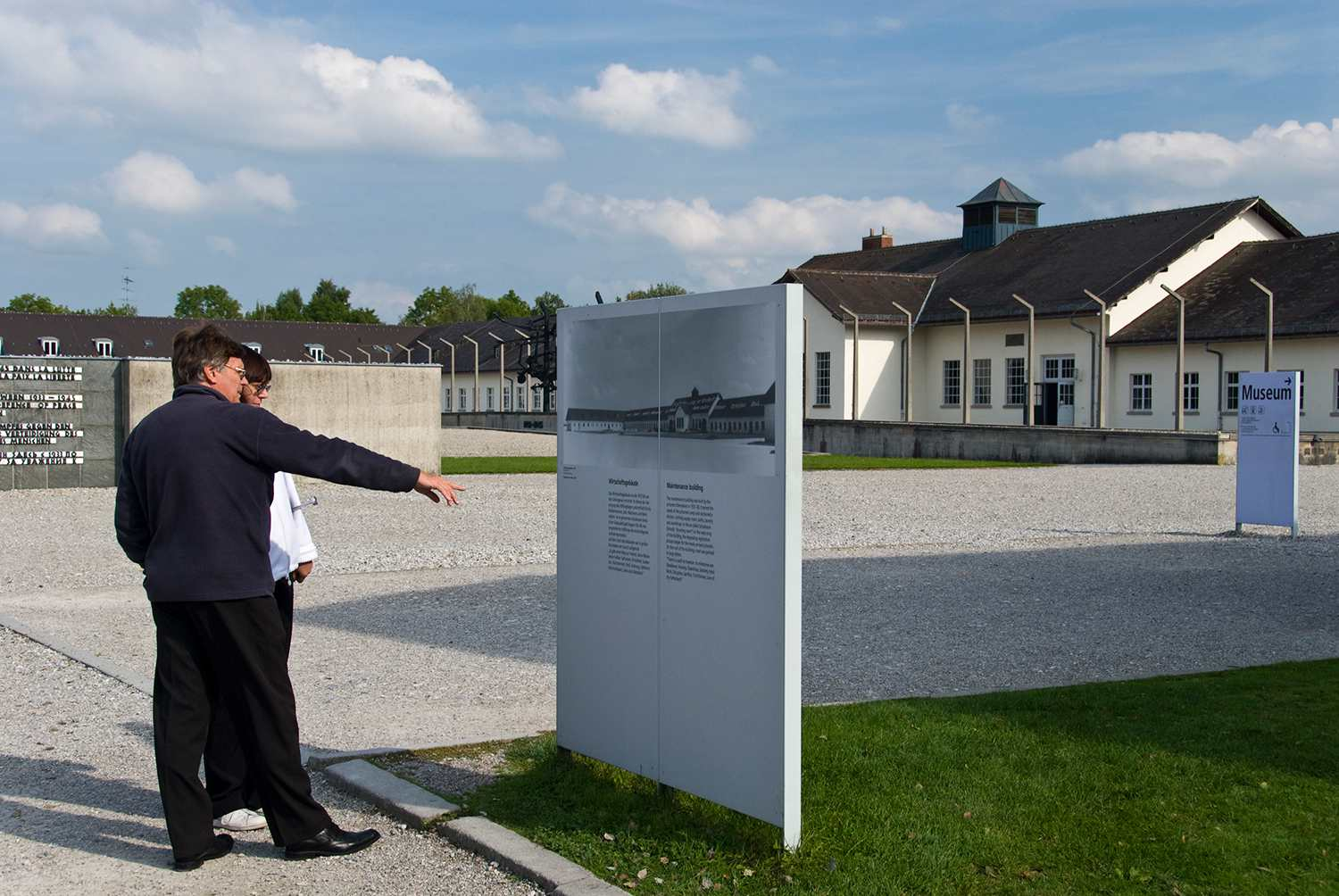 Tourists reading signage at near Dachau Concentration Camp Memorial entrance.