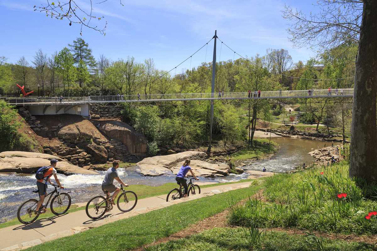 Three cyclist ride along the banks of a river with a suspension bridge overhead.