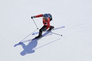 Aerial view of a female nordic cross country skier skiing across a frozen lake