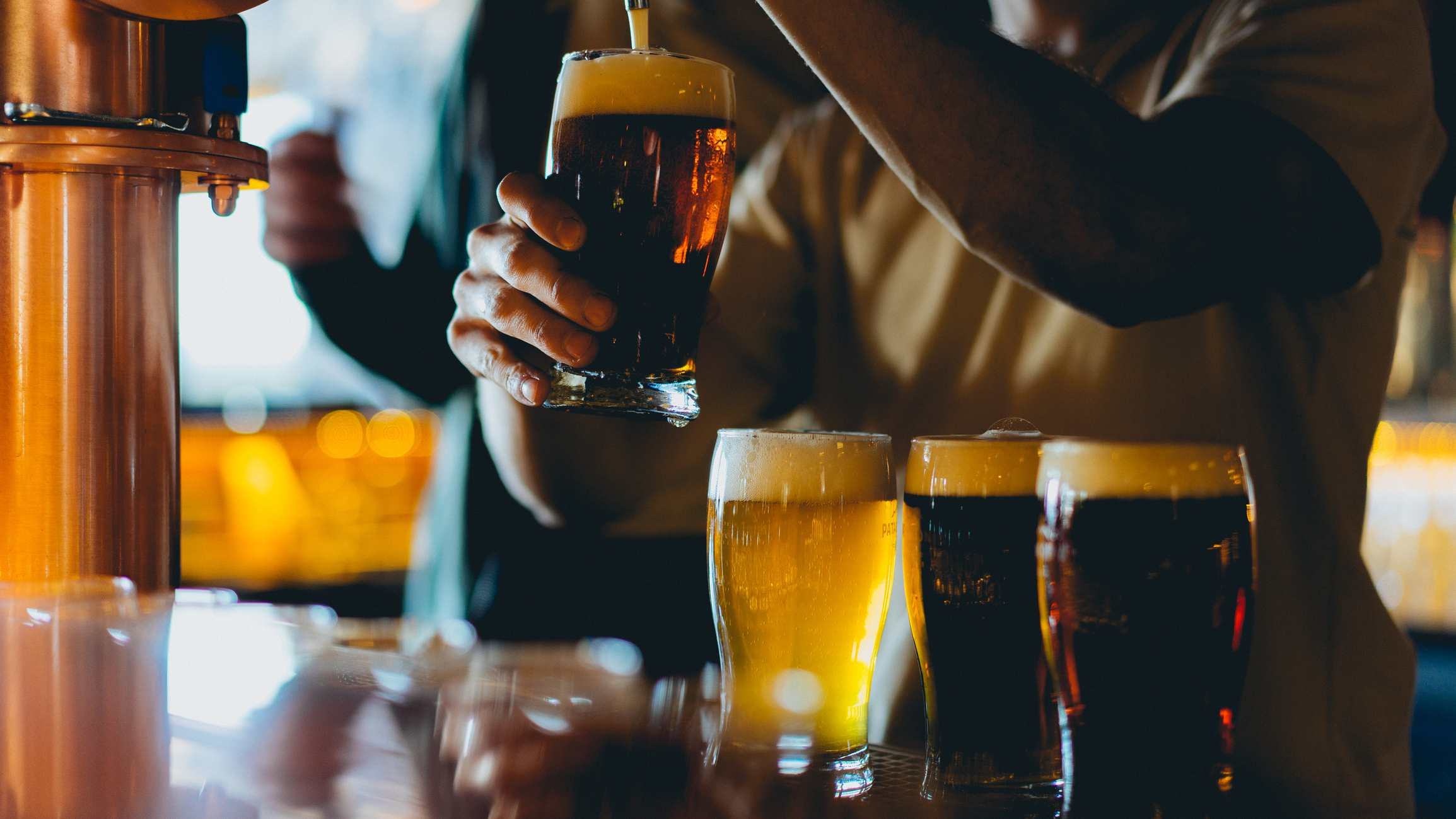 Man pouring beer into pint glasses