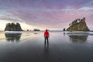 A man in a red jacket stands on beach with two rock outcroppings in the water.