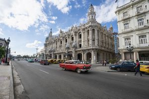 Vintage American cars on the street in front of the Galician Palace on Prado Street in Havana Cuba.