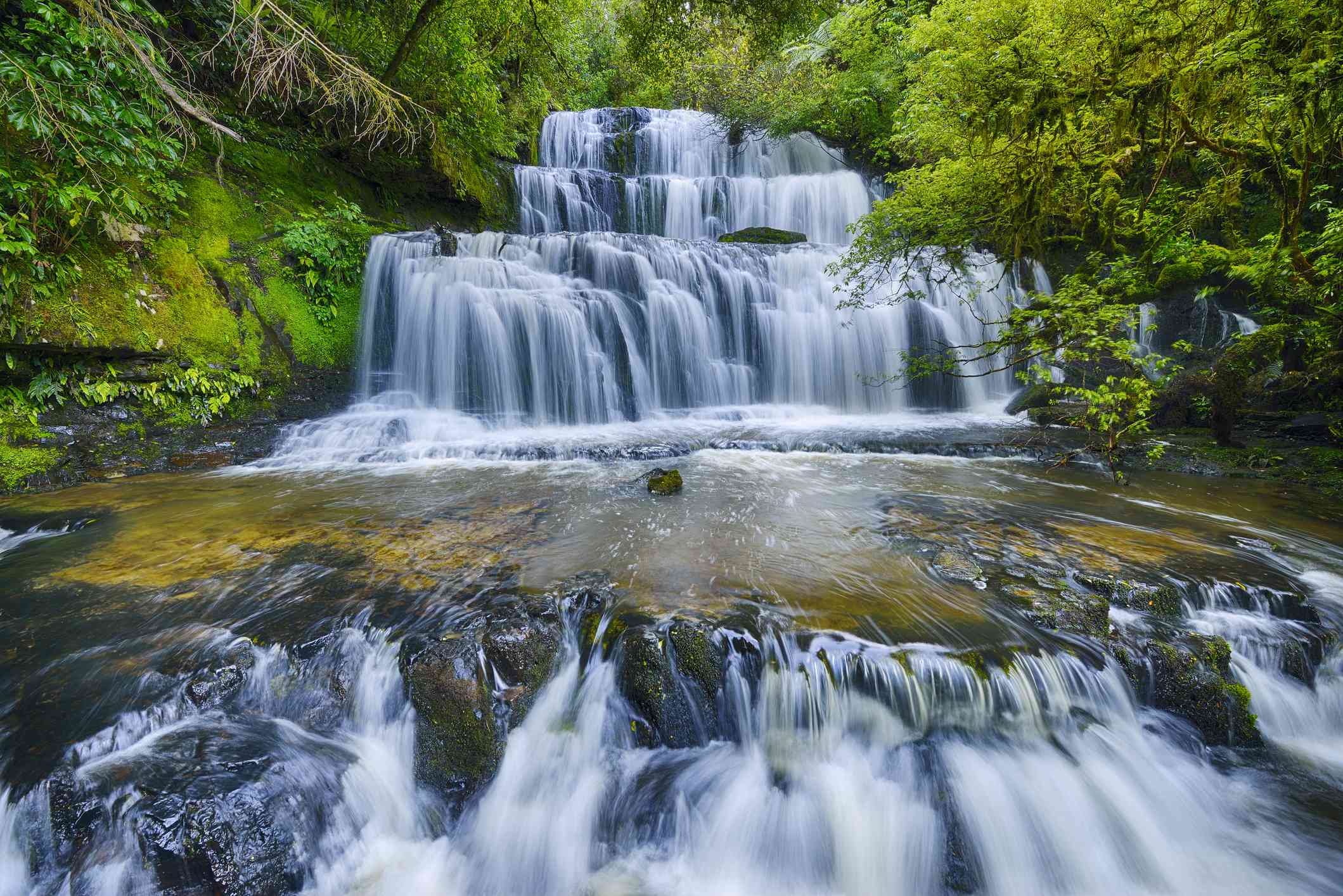 multi-tiered waterfalls surrounded by forest