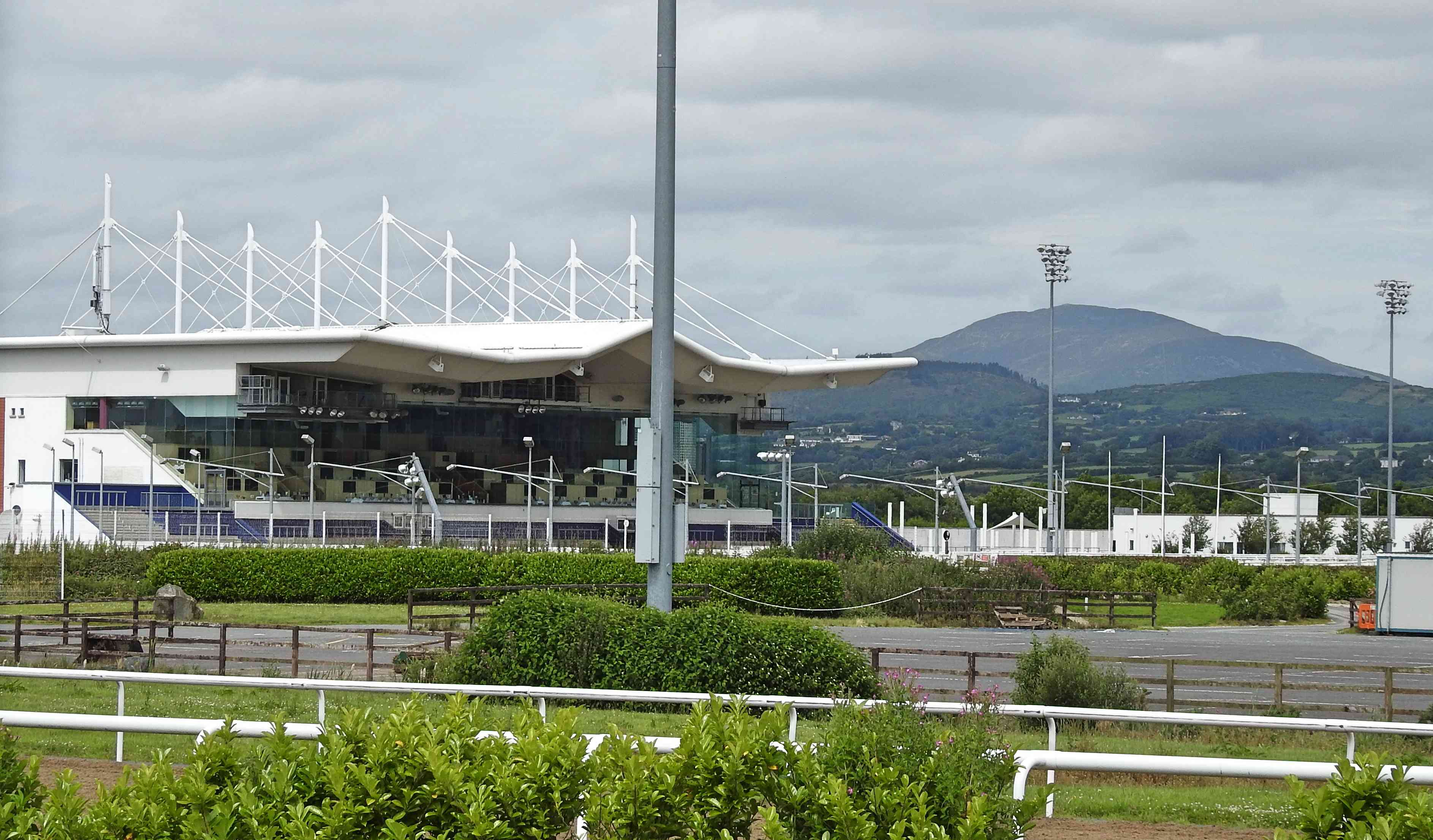 Outside Dundalk Stadium, a racecourse stadium for dog and horse racing with mountains in the background