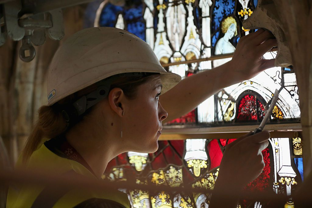 Stained glass conservator Lizzy Hippisley-Cox checks some of the finer details of the first section of the restored stained glass of the 600-year-old Great East Window of York Minster on August 12, 2015 in York, England. This rare view is approximately 78 feet up at the apex of York Minsters Great East Window and is the first competed section of the countrys largest single expanse of medieval stained glass.