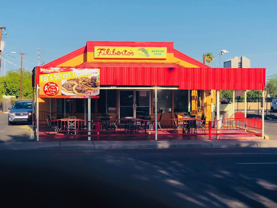 Red and yellow building with a covered patio and red fence. On the top of the building is a sign reading Filibertos Mexican Food with a picture of a taco