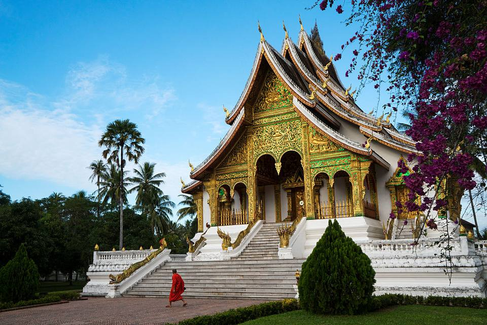 A Buddhist monk passes the Pha Bang Royal Palace Temple in Luang Prabang