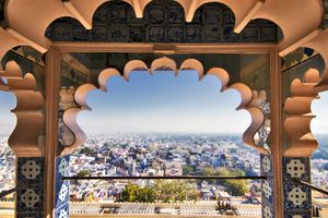 buildings in Udaipur seen from the city palace frramed by an archway