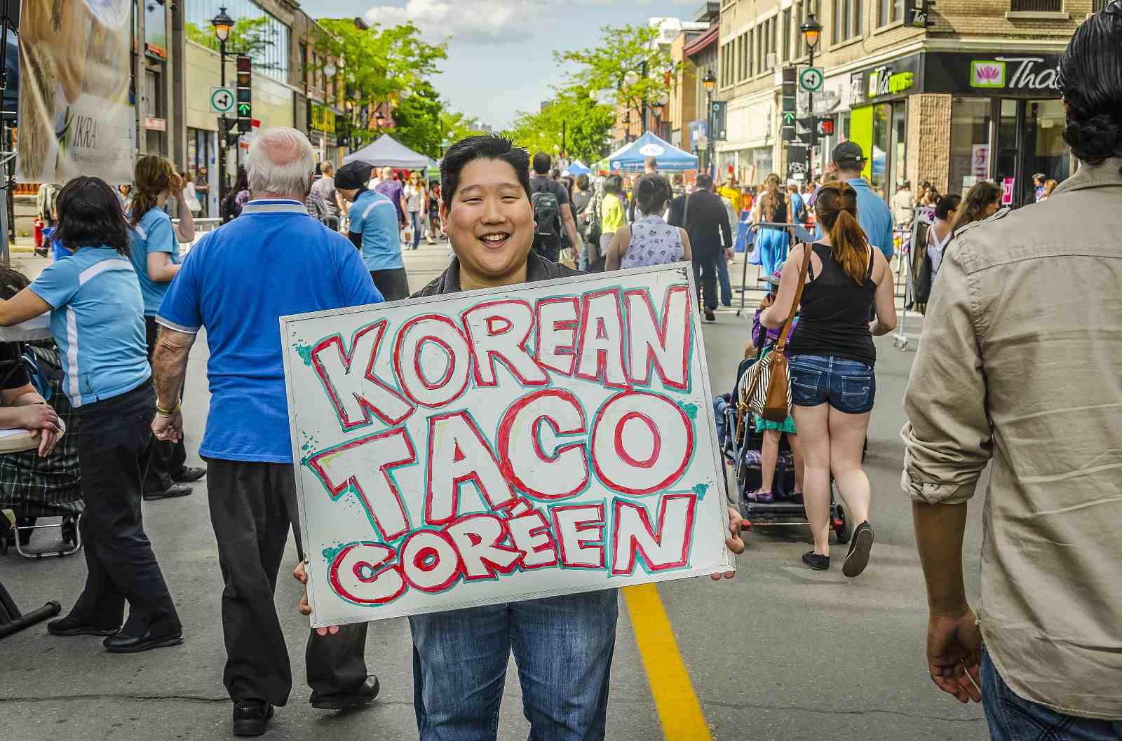 Montreal summer sidewalk sale vendor holding sign for Korean tacos