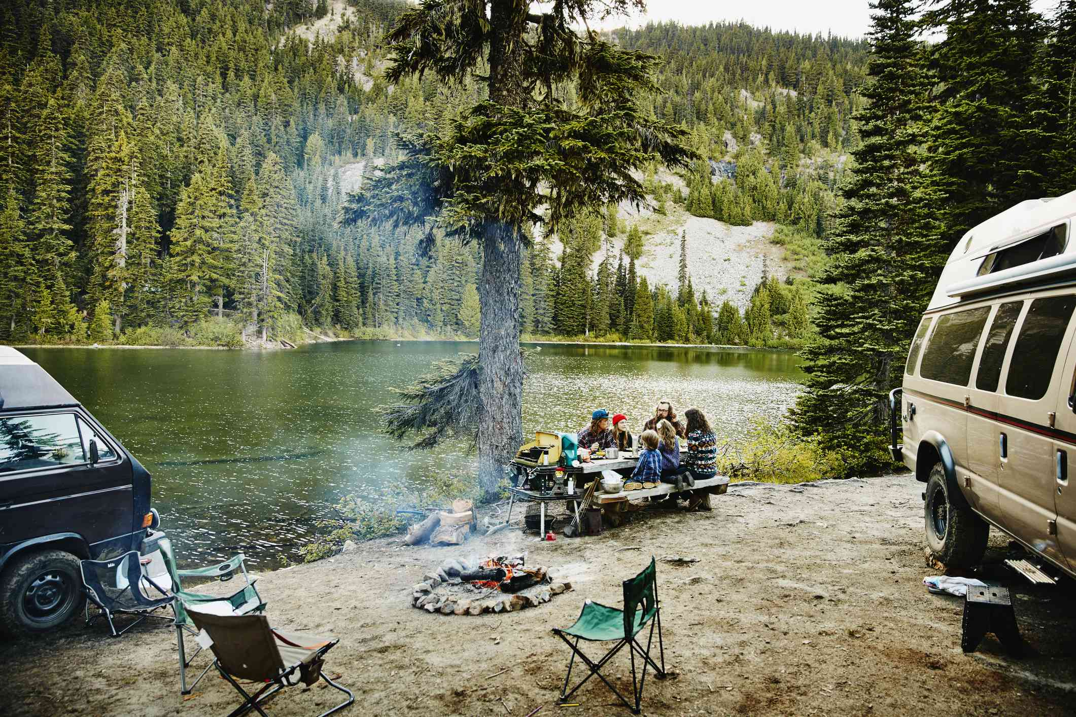 A family sitting at a campsite pinic table with two camping vehicles, and a smoldering fite pick with three foldable lawn chair around it