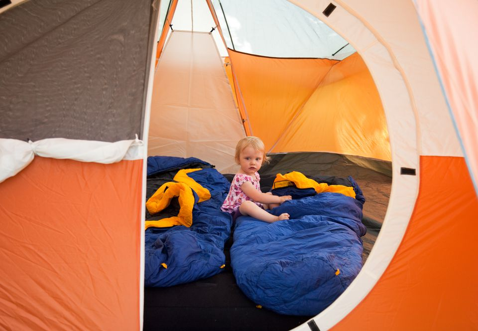 Little girl sitting on sleeping bag inside a tent.