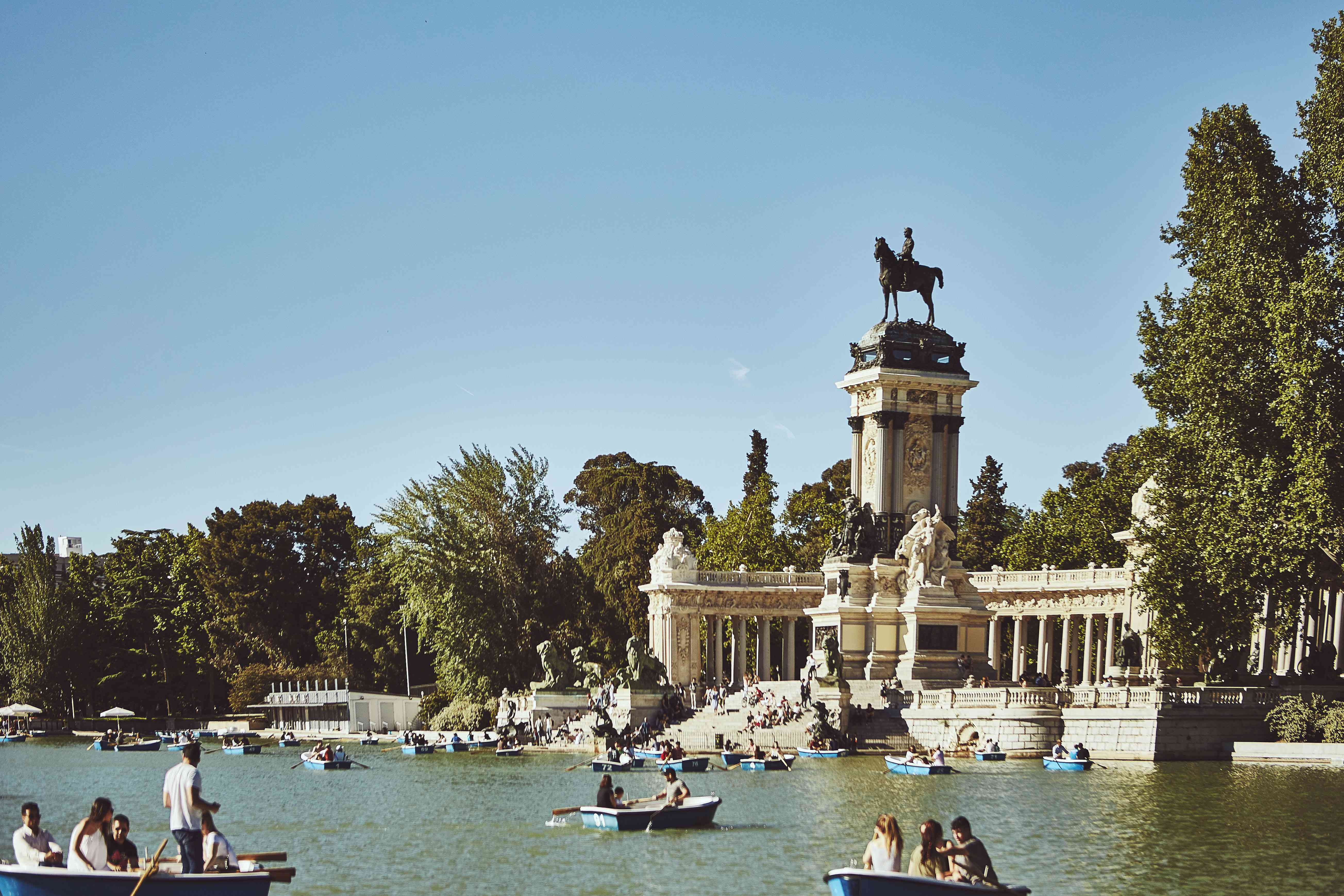 People rowing small boats around the lake in Buen Retiro Park