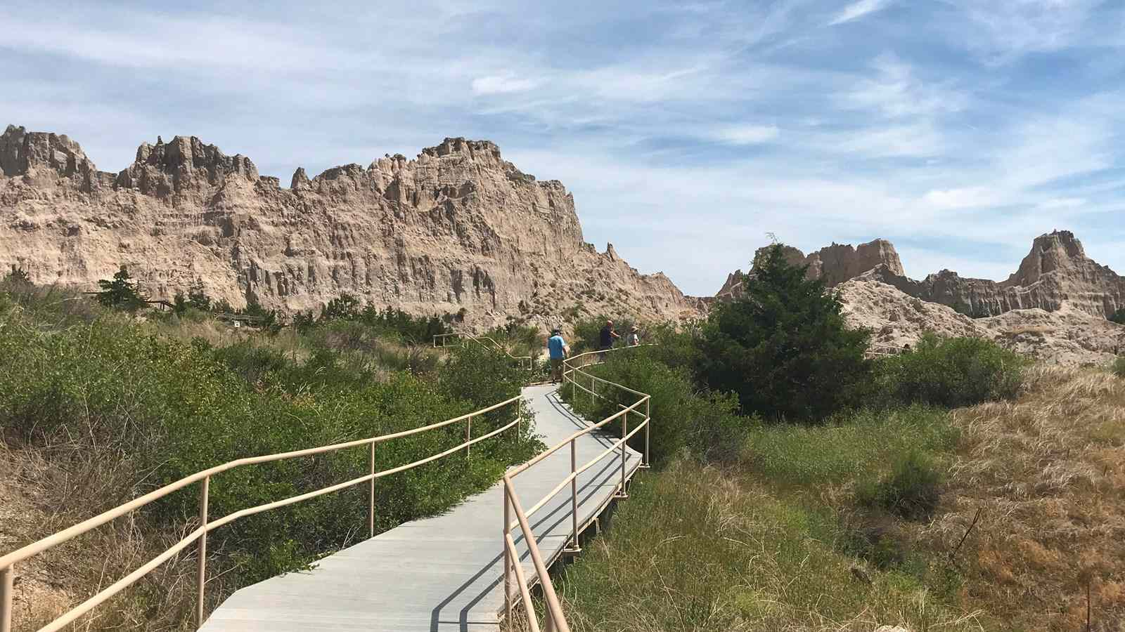 boardwalk trail through grass in Badlands national park with a person in the distance