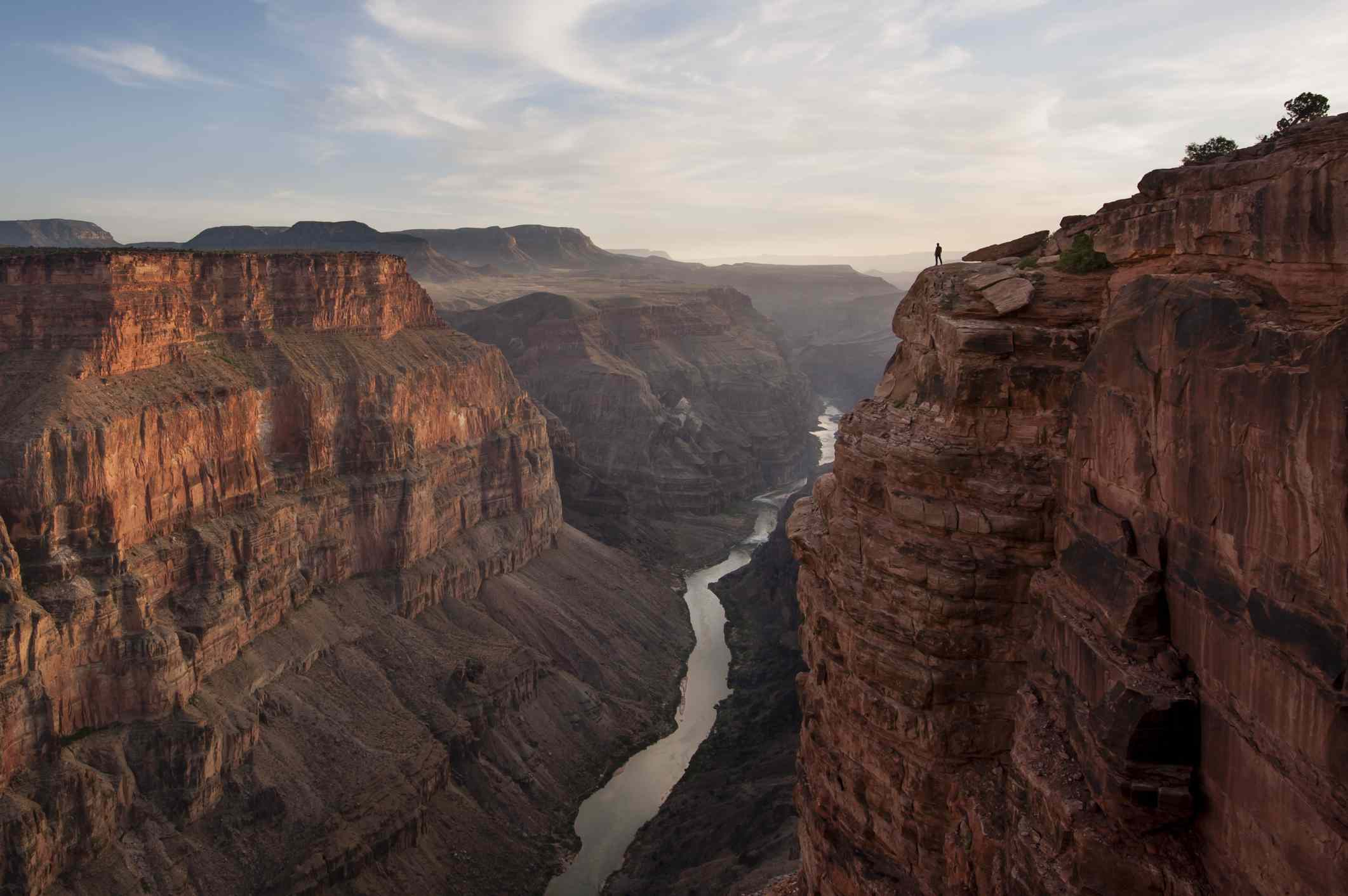 A man looking out over a canyon and river. Grand Canyon, Arizona