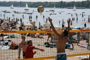 People enjoy the hot weather with a little volleyball at the beach of the Strandbad Wannsee.
