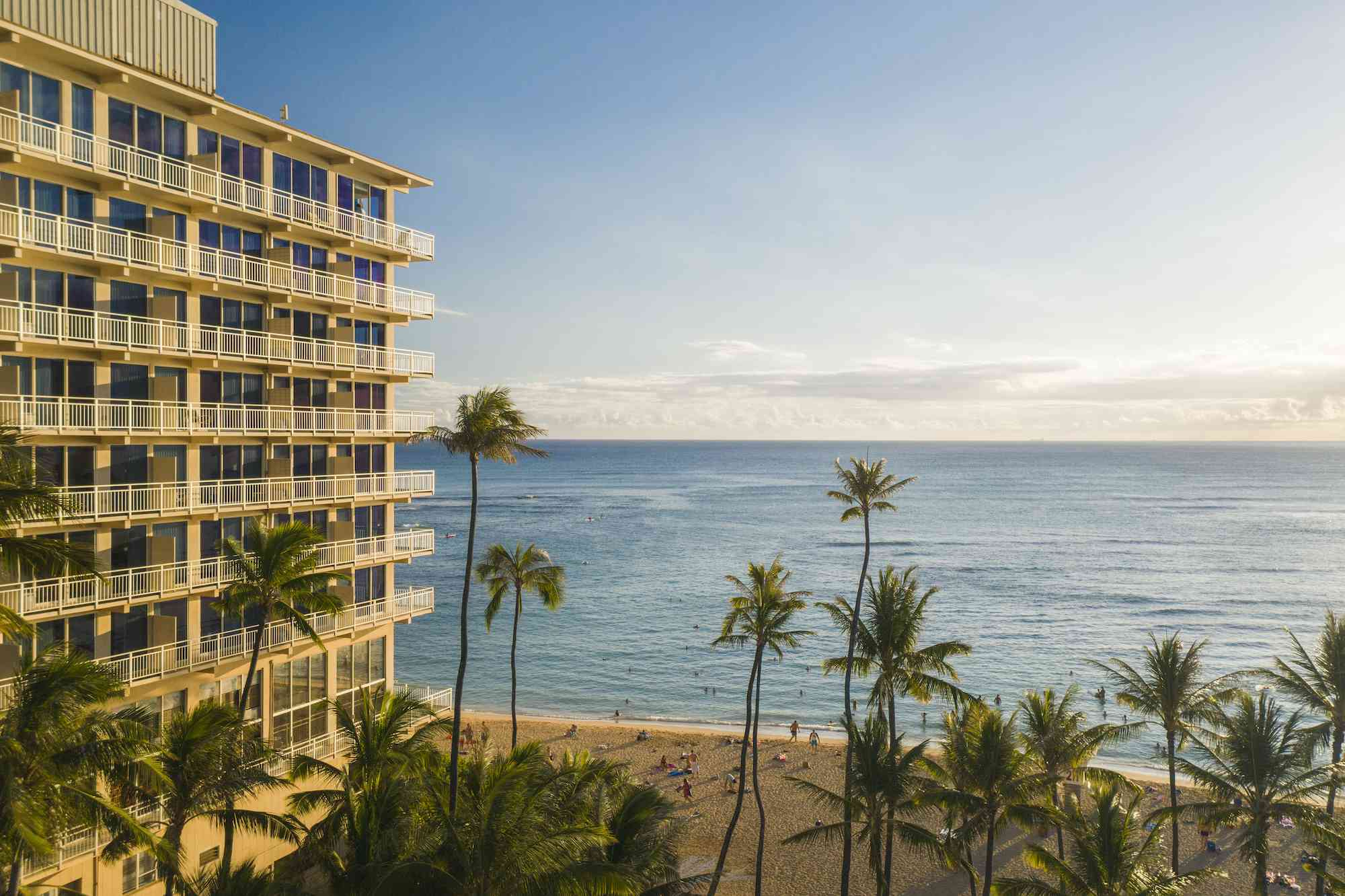 Exterior view of Kaimana Beach Hotel with the beach and water visible from the hotel's entrance
