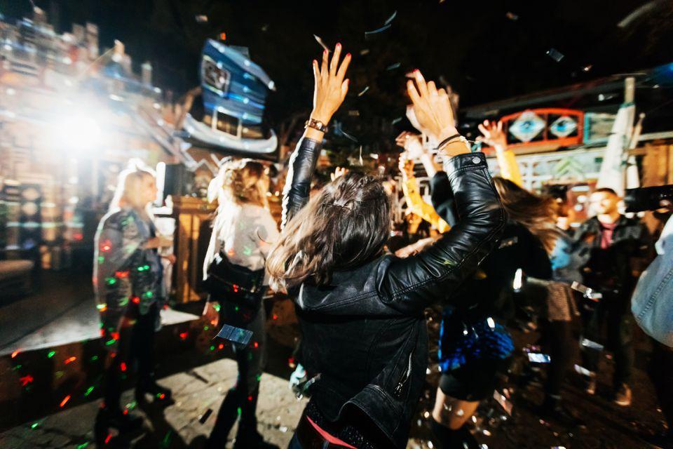 Mujer joven arrojando las manos en el aire mientras bailaba en la discoteca al aire libre en Berlín Alemania