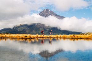 two people walking beside a lake with a volcano behind that's surrounded by white clouds
