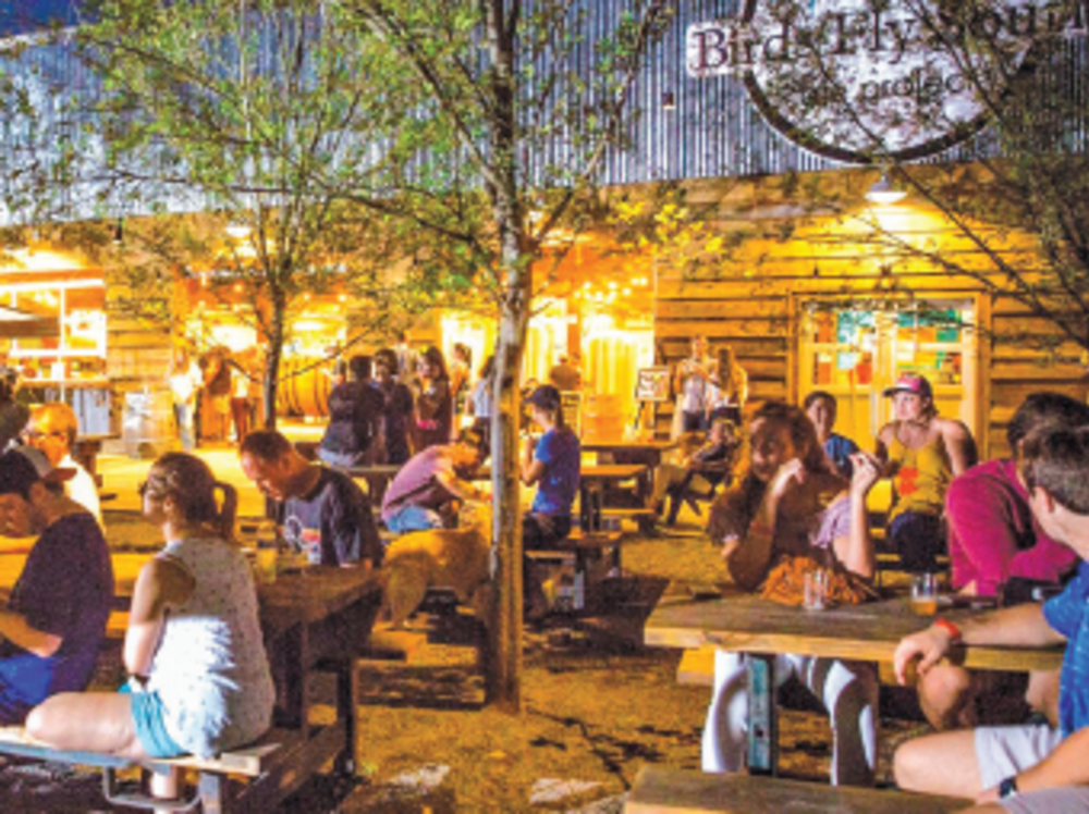 People sitting at outdoor bench tables at a brewery
