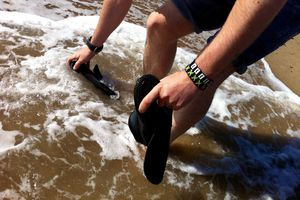Low Section Of Man Cleaning Shoes In Water In Sea