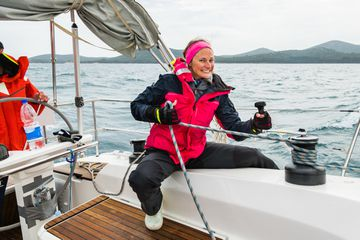 Smiling Adult Woman Pulling Rope on Sailboat