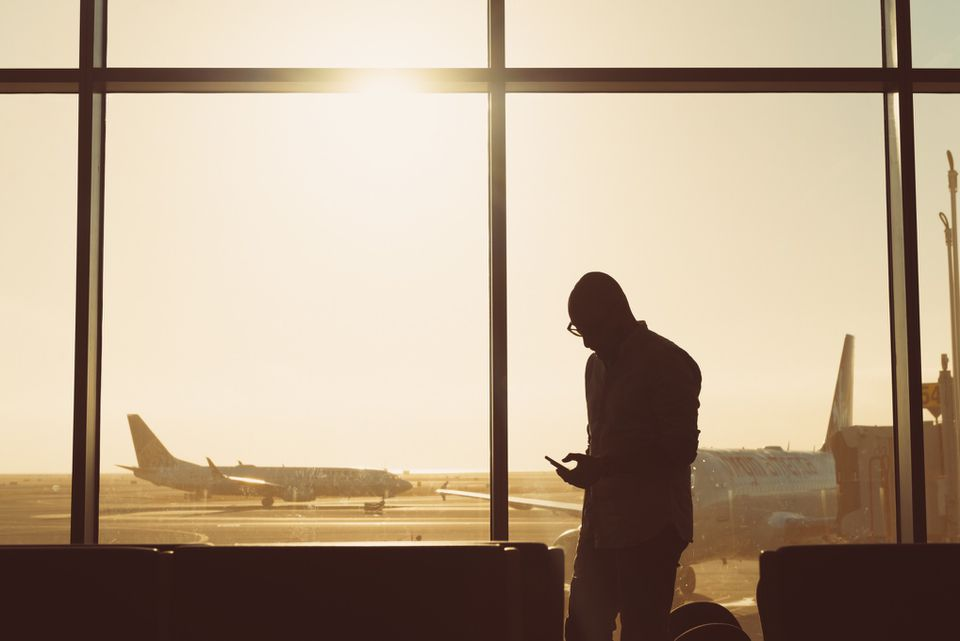 Man waiting in an airport. He's backlit from sunset and through the window you can see two planes