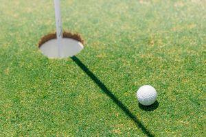 A golf club near the hole on the green