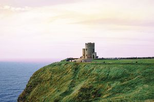 Tourist visiting Obrien Tower on Cliffs Of Moher by sea against cloudy sky