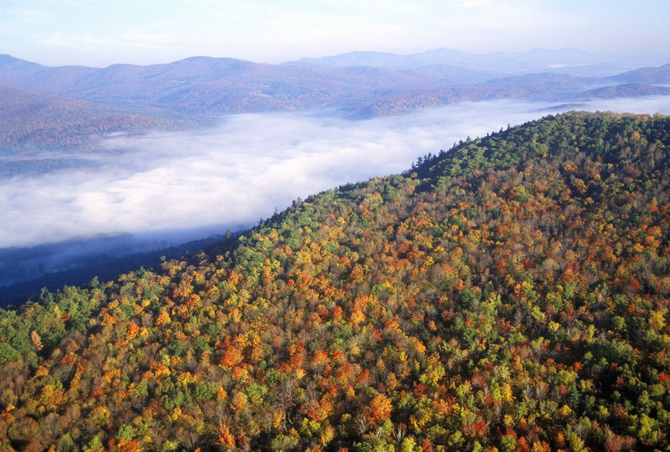 Aerial view of morning fog over mountains near Stowe, VT in autumn along Scenic Route 100
