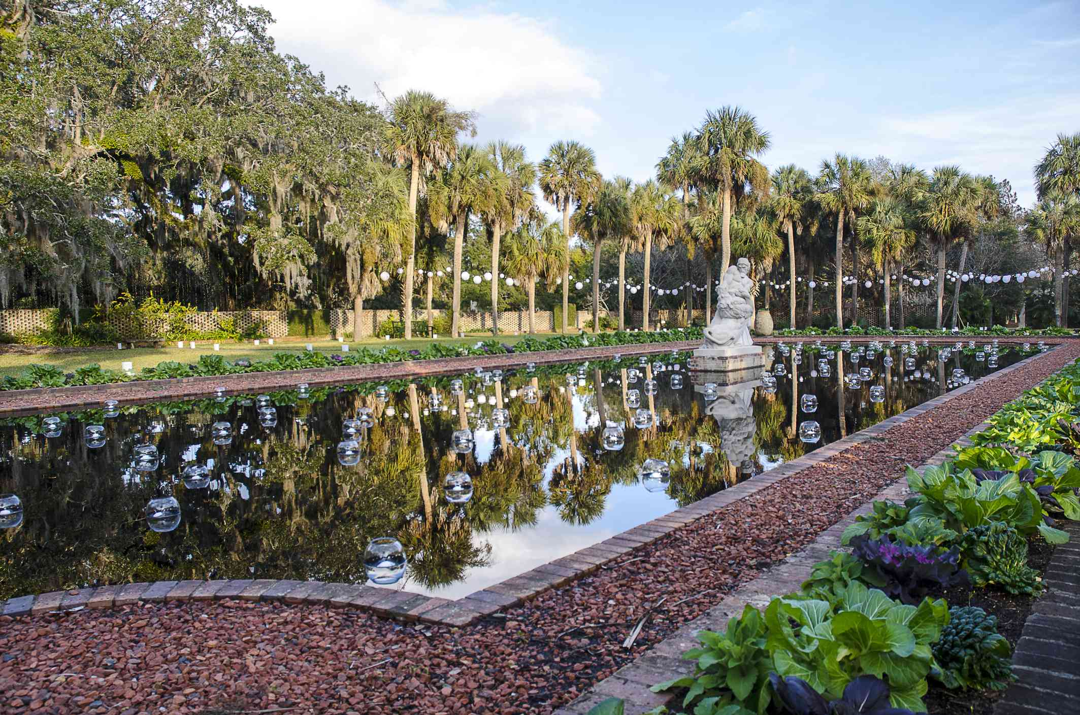 reflecting pool with a statue and glass orbs floating in it