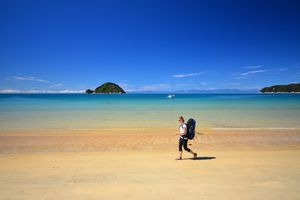 woman wearing backpack walking along a golden beach with blue sea and sky and an offshore island
